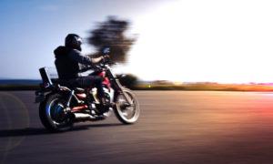 Un motard roulant face au couché de soleil